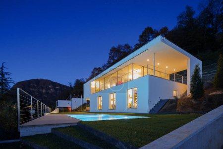 Photo pour Maison moderne, extérieur dans la nuit, lumières allumées - image libre de droit