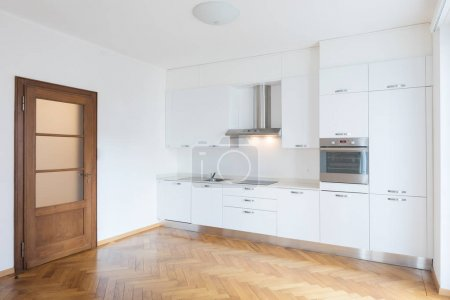Kitchen in newly renovated open space with wooden floors