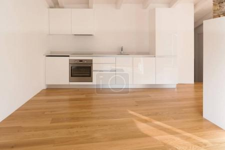 Photo for Front view of modern kitchen. Parquet floor and wooden beams - Royalty Free Image