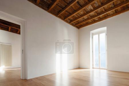 Photo pour Salle vide avec grande fenêtre donnant sur le lac. Anciennes poutres au plafond d'un appartement rénové - image libre de droit