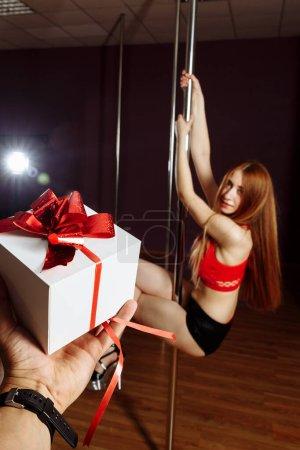 Photo pour Fille dans un strip-tease topdancing rouge et tenant un cadeau. fille dansant sur un pylône .. - image libre de droit