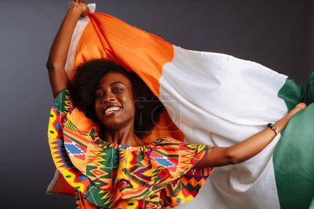Photo pour Bonne femme africaine en vêtements nationaux souriant et posant avec un drapeau Côte d'Ivoire, C te dIvoire isolé sur un fond gris .. - image libre de droit