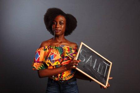 Photo pour Portrait d'une jeune étudiante africaine vêtue d'un tableau noir avec un bonjour dans sa propre langue maternelle isolée sur fond gris ... - image libre de droit