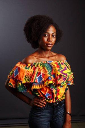Photo pour Jeune femme africaine de Côte d'Ivoire en vêtements traditionnels posant et souriant à la caméra .. - image libre de droit