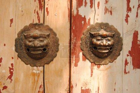 Photo pour Frappeurs de porte traditionnels chinois avec sembiance lion à Pékin Hutong, Chine - image libre de droit