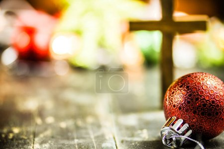 Photo for Traditional Christmas holiday ornaments and a holy Christian cross on a dark stained wooden floor background. - Royalty Free Image
