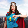 Pretty superhero girl making bad signal with the c...