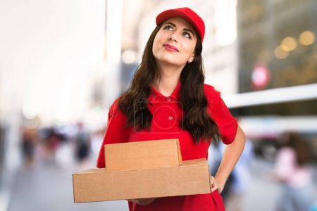 Young delivery woman looking up on unfocused background