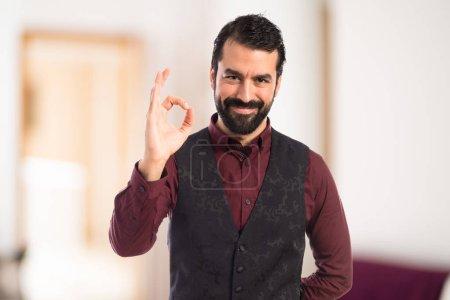 Man wearing waistcoat making Ok sign