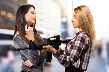 Two friends holding a rifle on unfocused background