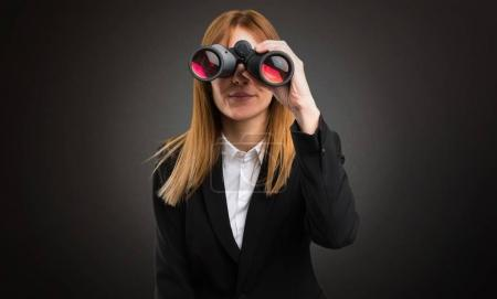 Young business woman with binoculars on dark background