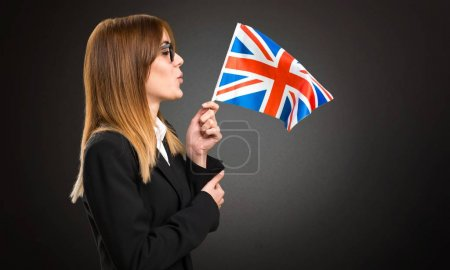 Young business woman holding an United Kingdom flag on dark background