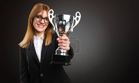 Young business woman holding a trophy on dark background