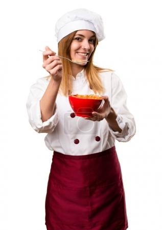 Happy Beautiful chef woman eating cereals from a bowl