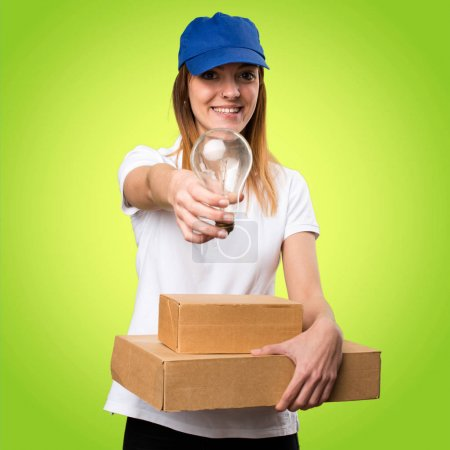 Delivery woman holding a bulb on colorful background