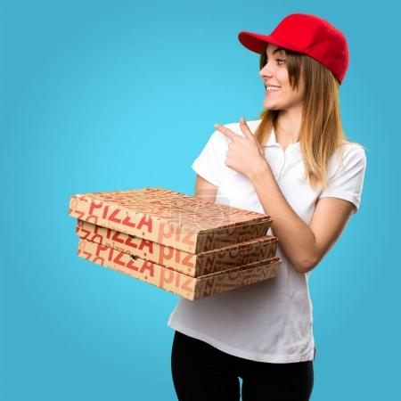 Pizza delivery woman  pointing back on colorful background