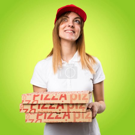 Pizza delivery woman looking up on colorful background