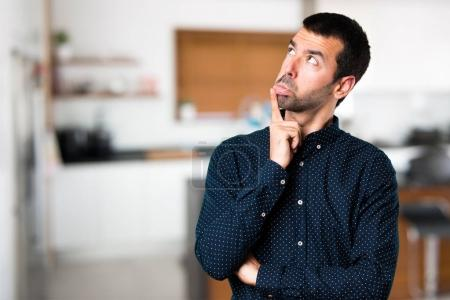 Handsome man having doubts inside house