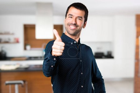 Handsome man with thumb up inside house