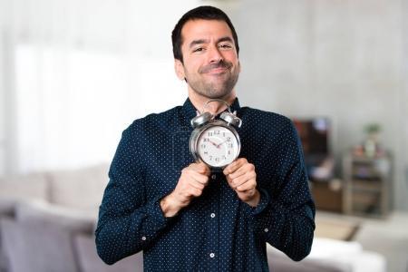 Handsome man holding vintage clock inside house