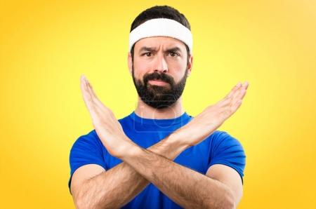 Funny sportsman making NO gesture on colorful background