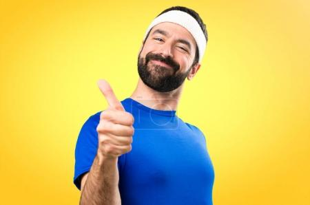 Funny sportsman with thumb up on colorful background