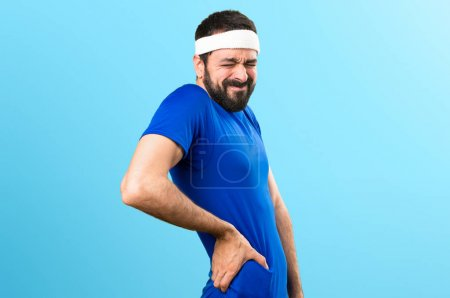 Funny sportsman with back pain on colorful background