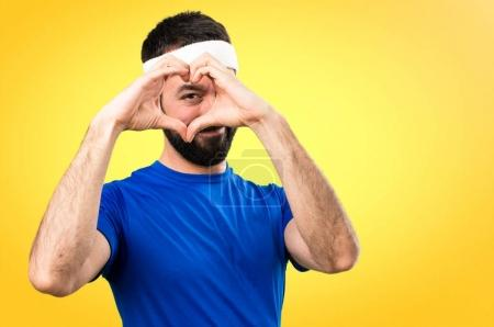Funny sportsman making a heart with his hands on colorful backgr