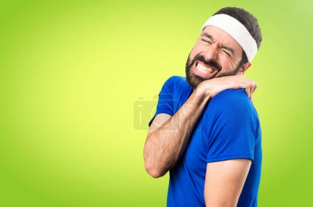 Funny sportsman with shoulder pain on colorful background