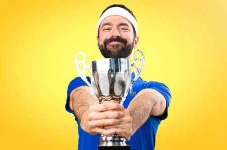 Funny sportsman holding a trophy on colorful background