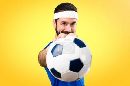 Funny sportsman holding a soccer ball on colorful background