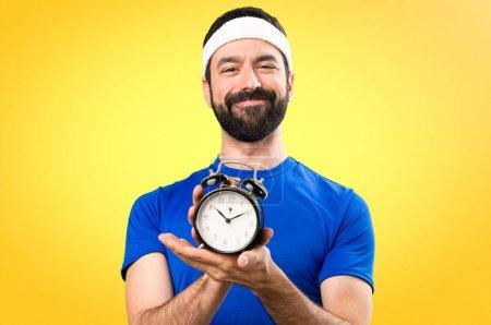 Happy Funny sportsman holding vintage clock on colorful backgrou