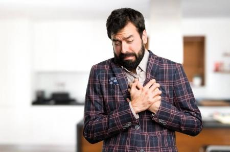 Well dressed man with heart pain inside house