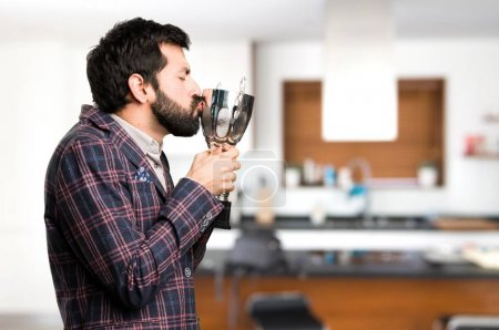 Happy Well dressed man holding a trophy inside house