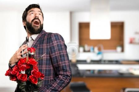 Surprised Well dressed man holding flowers inside house