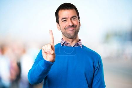 Handsome young man counting one on unfocused background