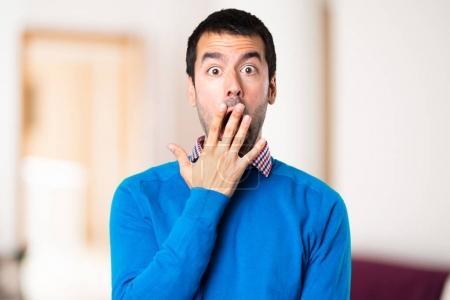 Handsome young man making surprise gesture on unfocused backgrou