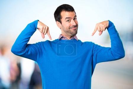 Foto de Atractivo joven apuntando hacia abajo en el fondo desenfocado - Imagen libre de derechos