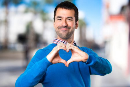 Handsome young man making a heart with his hands on unfocused ba
