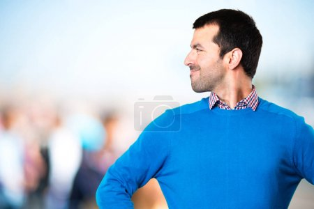 Handsome young man looking lateral on unfocused background