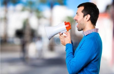 Handsome young man holding a megaphone on unfocused background