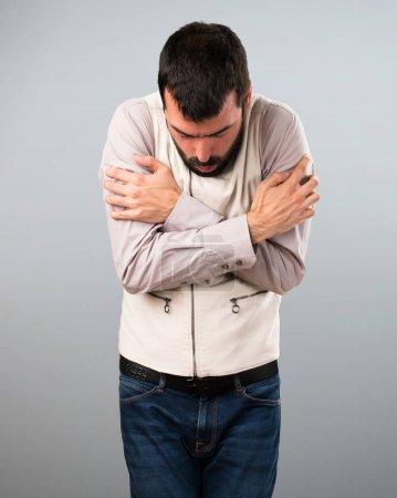Handsome man with vest freezing on grey background