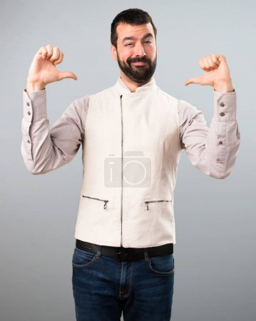 Handsome man with vest proud of himself on grey background