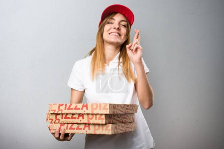 Pizza delivery woman with her fingers crossing on textured backg