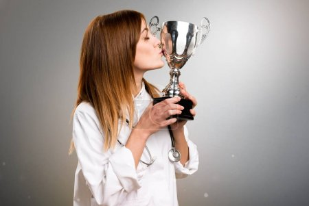 Young doctor woman holding a trophy on grey background