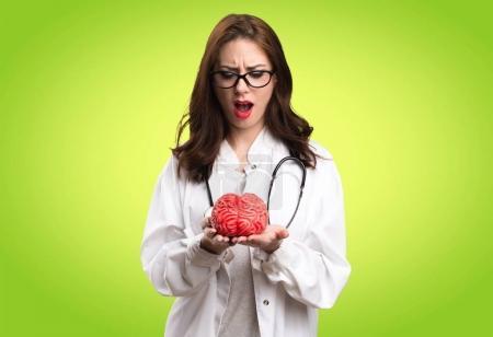 Photo pour Docteur femme tenant un cerveau sur fond vert - image libre de droit