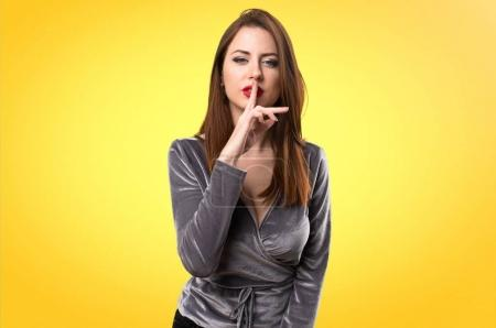Beautiful young girl making silence gesture on colorful background