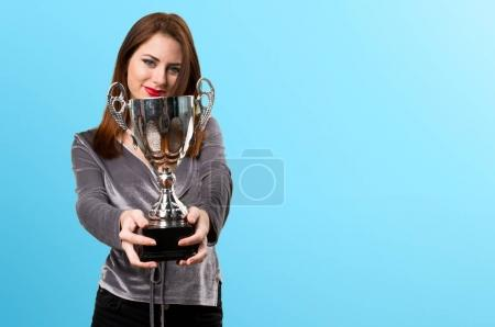 Beautiful young girl holding a trophy on colorful background