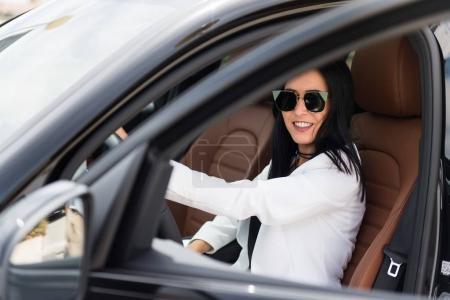 Beautiful young girl inside a luxury car