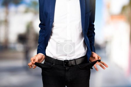 Ruined  handsome man  looking money in their pockets on unfocused background